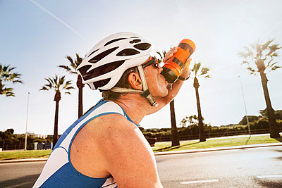 Spain, Mallorca, Sa Coma, portrait of triathlet drinking water on bicycle - p300m1028600f by Mareen Fischinger