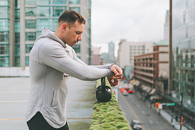 Man working out with a kettlebell in the city, Canada - p300m2169962 by Crystal Sing