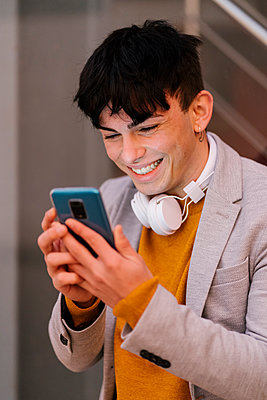 Young man smiling while using mobile phone standing outdoors - p300m2251542 by Ezequiel Giménez