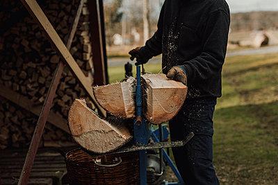 Man sawing log - p312m2191269 by Jennifer Nilsson