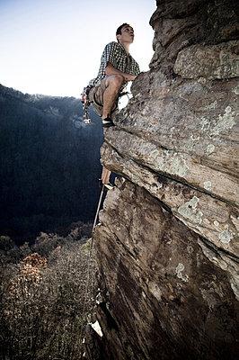A man climbs an airy arete - p3437409f by Andrew Kornylak