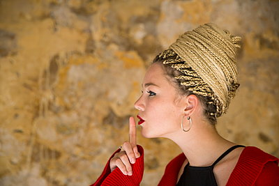 Profile of young woman with dreadlocks, finger to mouth - p429m1448121 by RUSS ROHDE