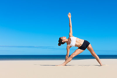 Woman on beach bending sideways arms raised in yoga position - p429m1494511 by Aziz Ary Neto