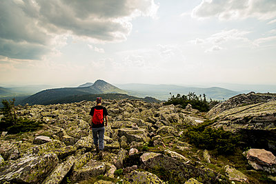 Caucasian hiker walking in rocky field in remote landscape - p555m1411149 by Aleksander Rubtsov