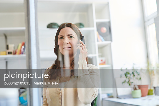 Businesswoman talking on smart phone seen through glass at office - p300m2189015 by Markus Mielek