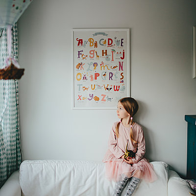 Girl sitting in kids room looking out of the window - p1414m1590581 by Dasha Pears