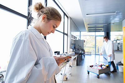 Young female chemist using digital tablet in a chemical laboratory - p300m981105f by Sigrid Gombert