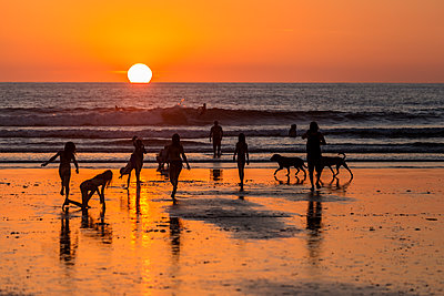 Playa Guiones, Silhouettes of people on beach at sunset in Costa Rica - p352m2120824 by Oskar Kihlborg