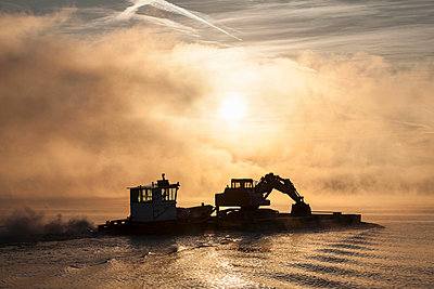 Silhouette of excavator on barge,  Lake Maggiore, Stresa, Piemonte, Italy - p429m911533f by WALTER ZERLA