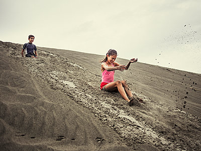 Children sliding on sand dune - p555m1312082 by Donald Iain Smith