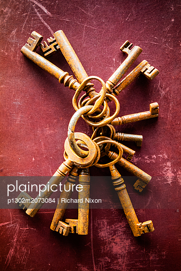 A large bunch of rusty old keys lying on a worn and scratched red surface - p1302m2073084 by Richard Nixon