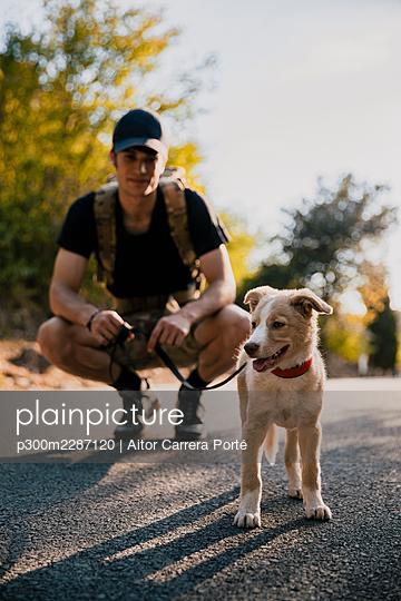 Boy walking his dog on a path in nature - p300m2287120 von Aitor Carrera Porté