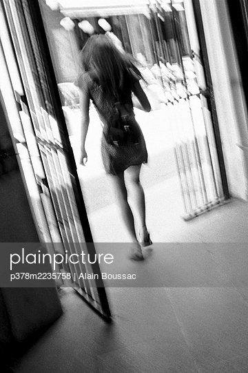 Young woman exiting doorway - p378m2235758 by Alain Boussac