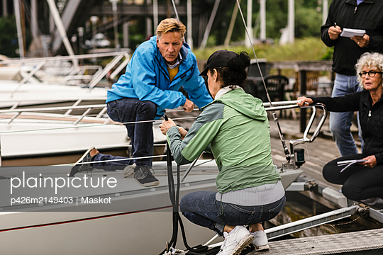 Senior man and woman looking at female instructor tying rope on railing of yacht during boat master course - p426m2149403 by Maskot