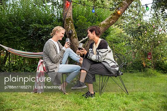 Zwei Freundinnen trinken Wein im Garten - p788m1165271 von Lisa Krechting