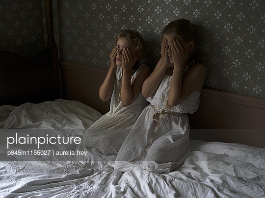 Zwei Mädchen auf dem Bett haben vor etwas Angst - p945m1155027 von aurelia frey