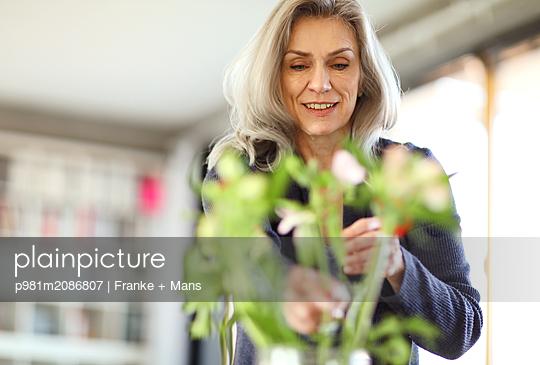 Blumen in die Vase stellen - p981m2086807 von Franke + Mans