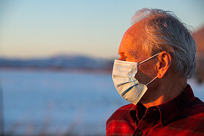 United States, Idaho, bellevue, Outdoor portrait of senior man wearing COVID protective mask in sunlight - p1427m2271688 by Steve Smith