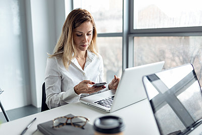 Businesswoman sitting in office working on laptop, using smartphone - p300m2170372 by Josep Suria