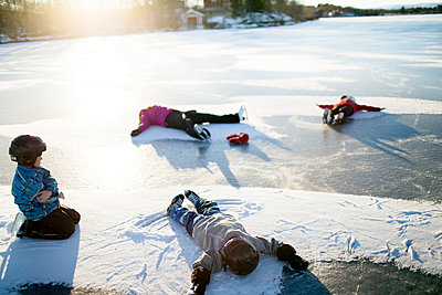 Mother with children making snow angels on frozen lake - p312m1472100 by Fredrik Ludvigsson