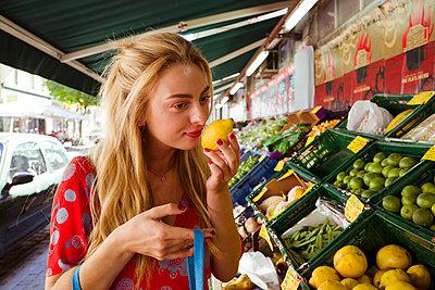 Junge Frau riecht an einer Zitrone - p432m1586242 von mia takahara