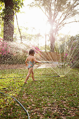 Girl in bathing costume playing in sunlit garden sprinkler water - p924m1422698 by Kinzie Riehm