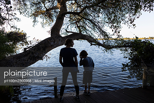 Two children on the edge of a waterway, rear view, Okavango Delta - p1100m2300968 by Mint Images