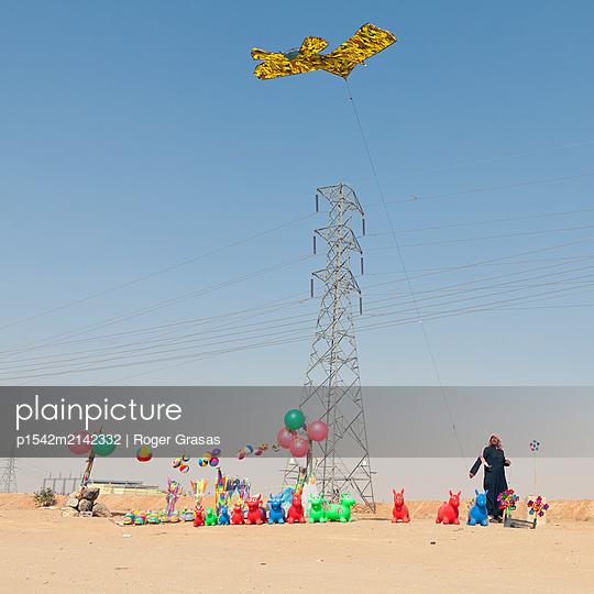 Souvenir Verkäufer in der Wüste lässt Drachen steigen - p1542m2142332 von Roger Grasas