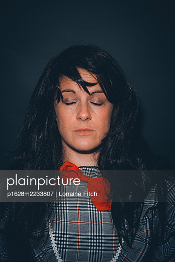 Long black haired woman with red tie and eyes closed - p1628m2233807 by Lorraine Fitch