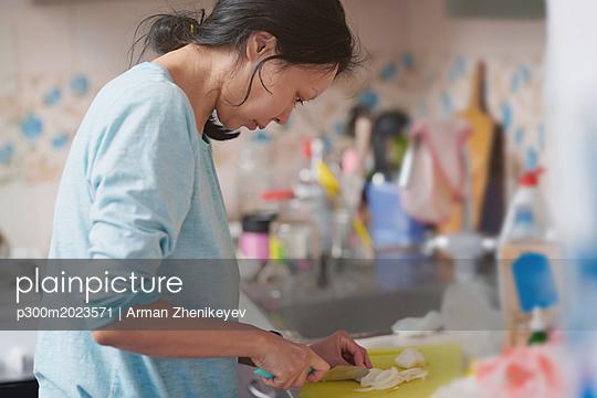 Woman chopping onion in the kitchen - p300m2023571 von Arman Zhenikeyev