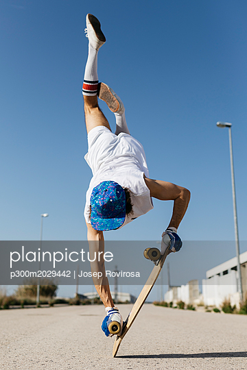 Back view of man in stylish sportive outfit standing on skateboard upside down against blue sky - p300m2029442 von Josep Rovirosa