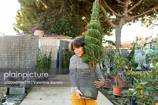 Portrait of boy carrying potted plant at plant nursery - p300m2156770 by Valentina Barreto