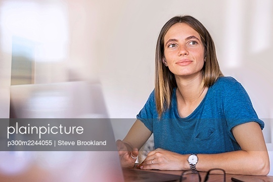 Thoughtful female professional sitting with laptop while working at home - p300m2244055 by Steve Brookland