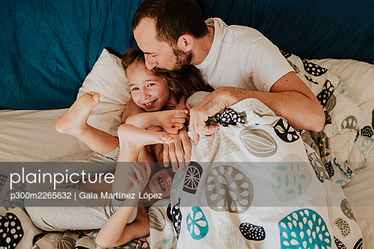 Father kissing daughter on forehead while son laughing on bed at home - p300m2265632 by Gala Martínez López