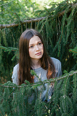 Junge Frau zwischen Tannenzweigen, Portrait - p1358m1215603 von Nolting