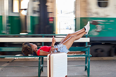 Woman with suitcase lying on a bench at the train station - p300m2104094 by Veam