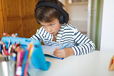 Boy doing homeschooling and writing on notebook, using tablet and headphones at home - p300m2188716 by Epiximages