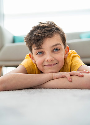 Close-up of smiling boy lying on carpet in living room - p300m2206986 by SERGIO NIEVAS