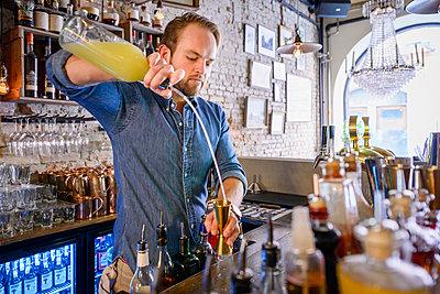 Barman preparing drink behind bar - p312m1103961f by Karl Forsberg