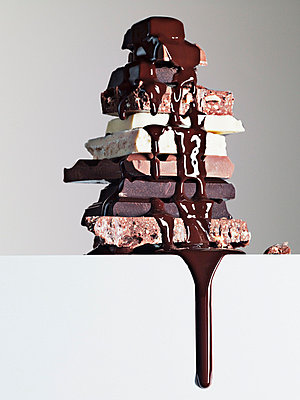 Chocolate syrup dripping over stack of chocolate bars - p64113811f by Martin Barraud