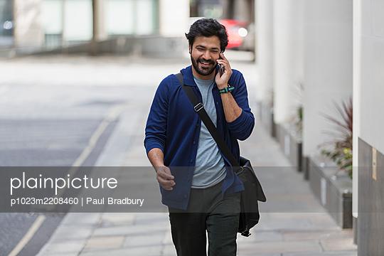 Businessman talking on smart phone on city sidewalk - p1023m2208460 by Paul Bradbury
