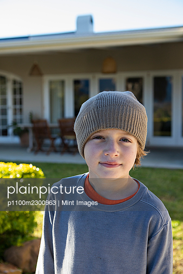 Portrait of a boy wearing a woolly hat. - p1100m2300963 by Mint Images