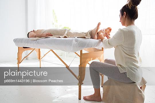 Female Massage Therapist Giving Man Foot Massage