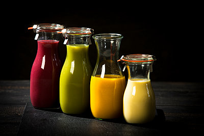 Four glass bottles of different smoothies - p300m2012869 by Roman Märzinger