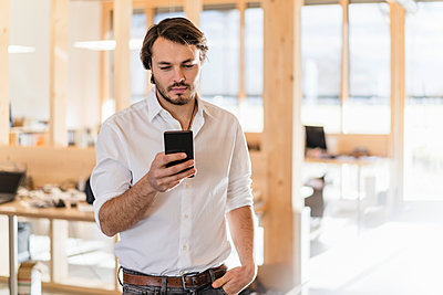 Businessman using cell phone in wooden open-plan office - p300m2170661 by Daniel Ingold