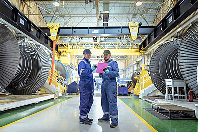 Engineers in discussion in turbine maintenance factory - p429m1547664 by Monty Rakusen
