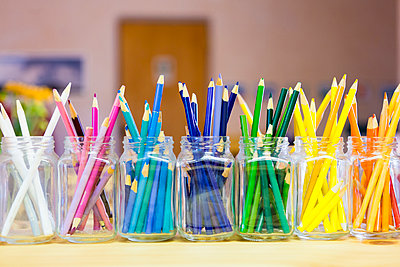 Close up of multicolor pencils organized in jars - p555m1410246 by Marc Romanelli