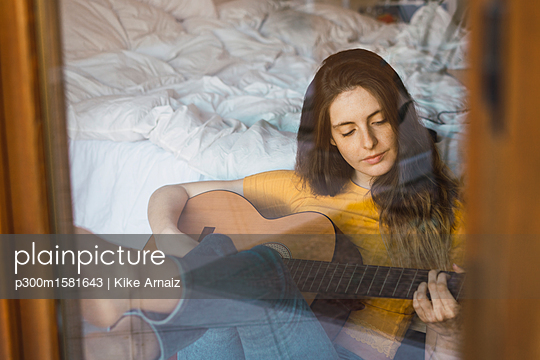 Portrait of relaxed young woman sitting behind windowpane playing guitar - p300m1581643 von Kike Arnaiz
