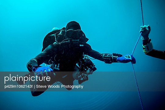 Underwater view of technical diver using a rebreather device to locate shipwreck, Lombok, Indonesia - p429m1062143f by Steve Woods Photography