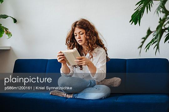 Junge Frau mit roten Haaren liest ein Buch - p586m1200161 von Kniel Synnatzschke